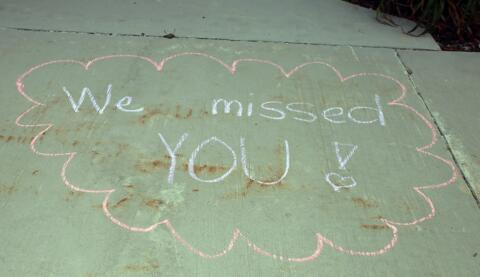 """we missed you"" written in chalk on the sidewalk"