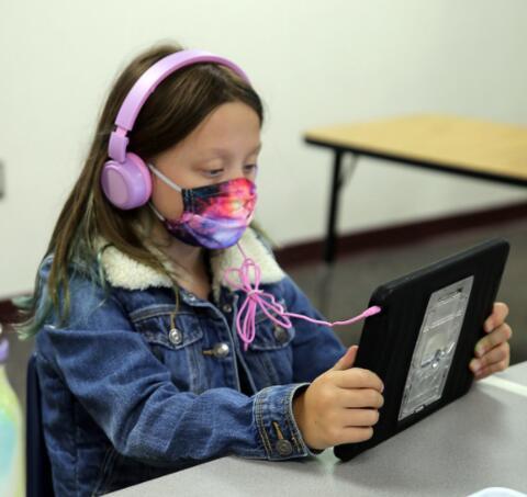 girl wearing headphones and working on her ipad