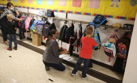 classroom aides helping students by their classroom hooks and backpacks
