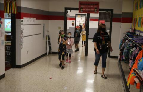 classroom aide and students walking in the hallway