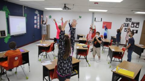 teacher and students in the classroom stretching