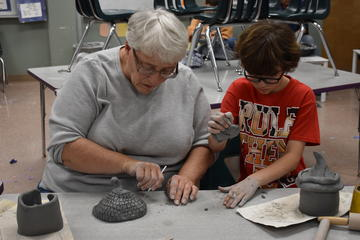 Family members work together on a clay fairy house.