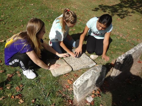 Students read inscription of a cemetery stone.