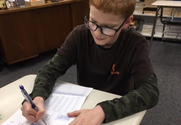 Sixth-grade Citizenship student Adam Burgio filling out a registration form.