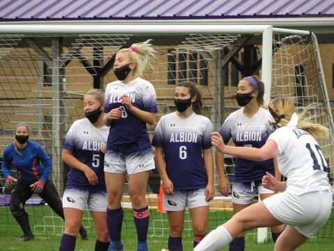 Girls make a wall to block the net.