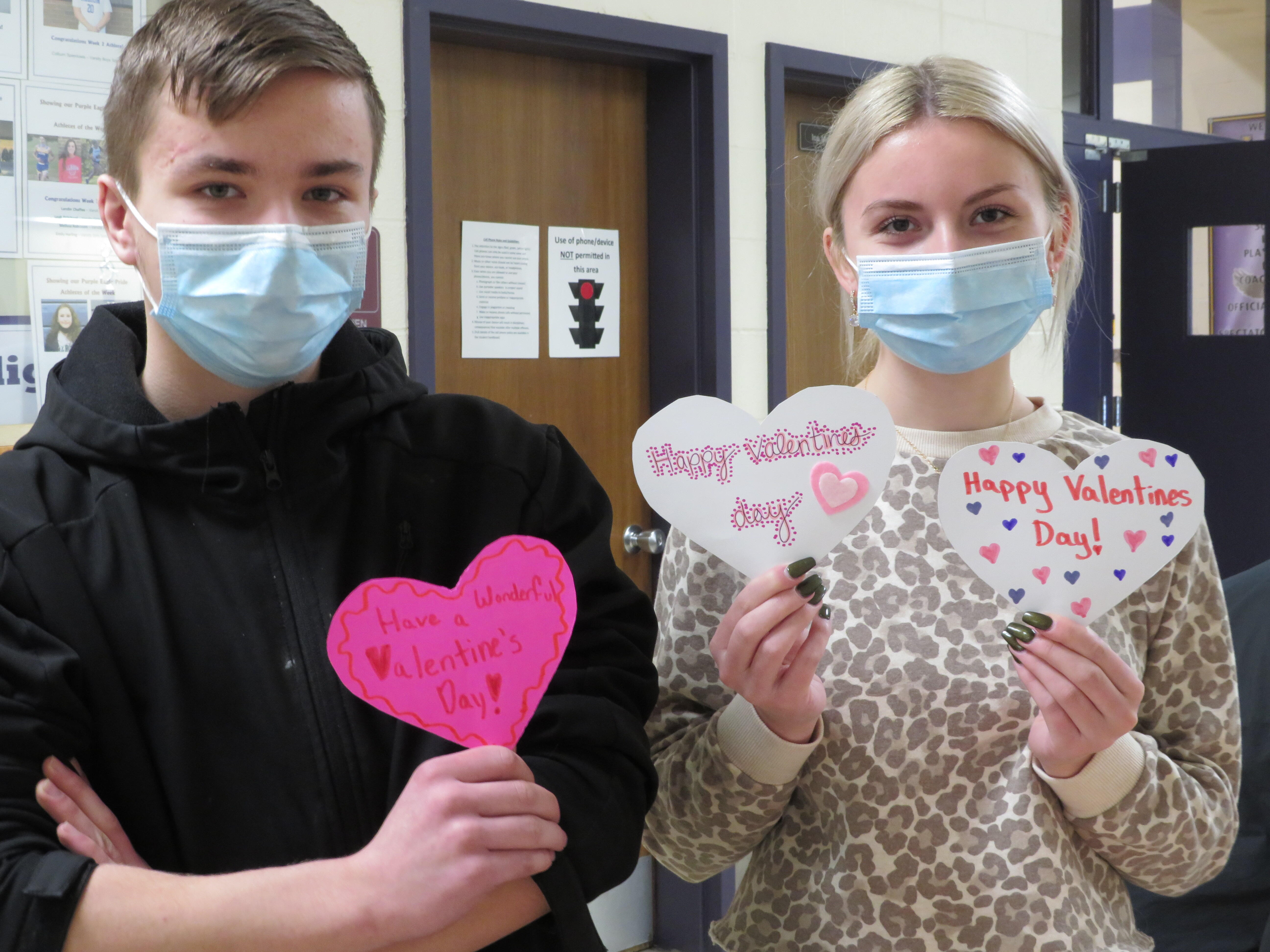 Owen Hunt (left) and Brittany Spies-Hunt (right) holding up valentines they made for the community.
