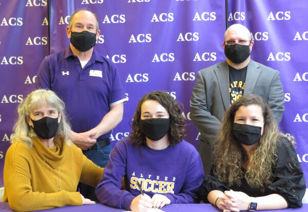 Claire Squicciarini (center) signs a letter of intent to play soccer at Alfred University.