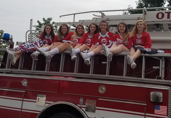 cheerleaders ride on fire truck